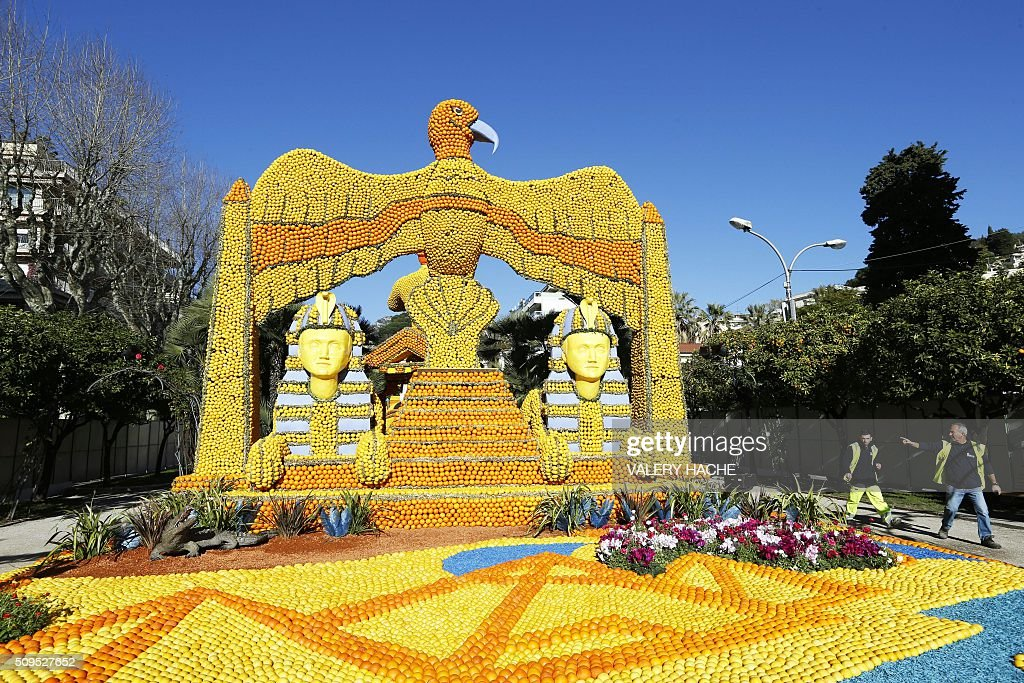 Workers walk past a giant sculpture decorated with oranges and lemons in Menton on the French Riviera on February 11, 2016, ahead of the start of the 'Fete du Citron' (Lemon Festival). The theme of this 83rd edition, running from February 13 until March 2, 2016, is called 'Cinecitta'. / AFP / VALERY HACHE