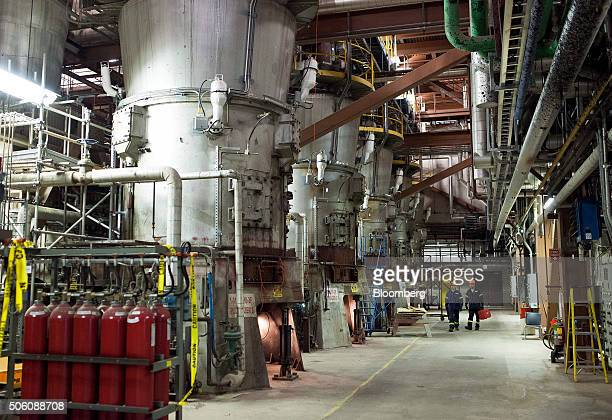 Workers walk past giant pulverizers that were once used to grind coal but have been converted to pulverize the biomass into a fine powder at the...
