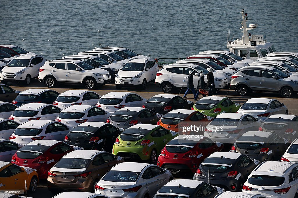 Workers walk past Hyundai Motor Co vehicles bound for export at a port near the company's plant in Ulsan South Korea on Thursday Jan 23 2014 Hyundai...