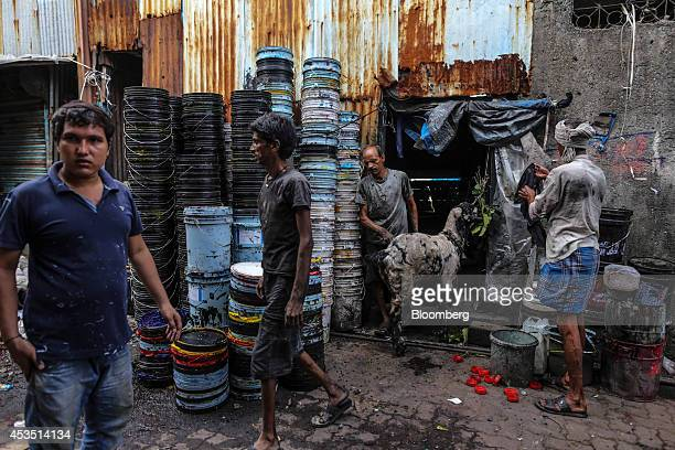 Workers walk past stacked plastic buckets for recycling and a goat in the Dharavi slum area of Mumbai India on Monday Aug 11 2014 Almost a year after...