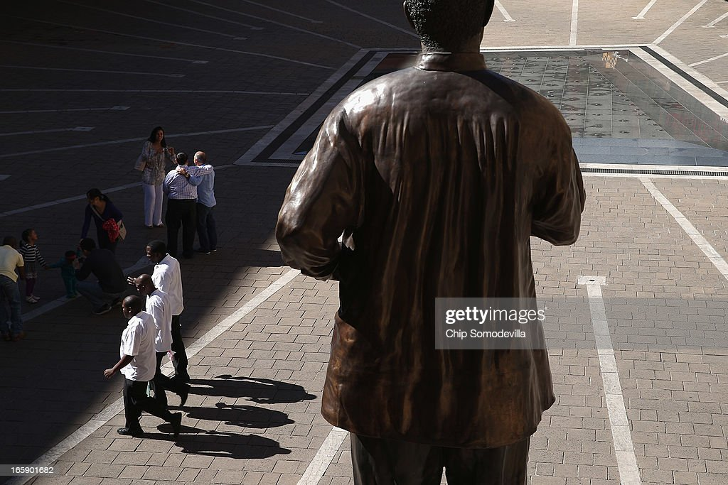 Workers walk past the 20-foot-tall statue of former South African President Nelson Mandela in Mandela Square near the Sandton shopping district on April 7, 2013 in Johannesburg, South Africa. Mandela returned to his Johannesburg home yesterday after spending nine days in the hospital with pneumonia.