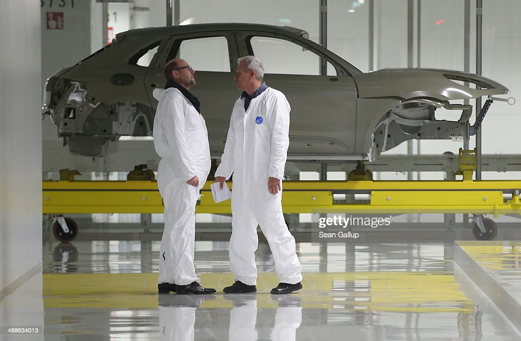Workers walk past the body of a Porsche Macan SUV at the new Porsche Macan factory at the Porsche plant on February 11, 2014 in Leipzig, Germany. Porsche plans to produce 50,000 of the new small SUV Macan annually.