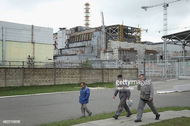Workers walk past the remains of reactor number four at the former Chernobyl nuclear power plant on September 29 2015 near Chornobyl Ukraine On April...