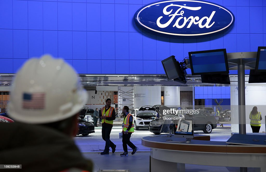 Workers walk through the Ford Motor Co. exhibit during an advance tour of the North American International Auto Show (NAIAS) at Cobo Hall in Detroit, Michigan, U.S., on Thursday, Jan. 10, 2013. More than 23,000 attendees representing almost 2,000 companies are expected to attend the industry preview for NAIAS on Jan. 16-17. The general public can attend the show from Jan. 19-27. Photographer: Jeff Kowalsky/Bloomberg via Getty Images