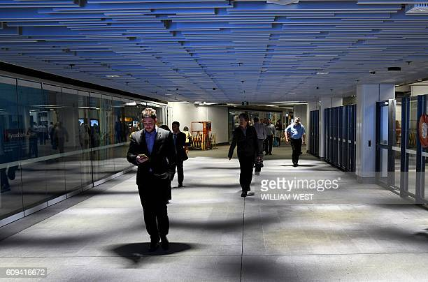 Workers walk to the developing office and residental area of Barangaroo in Sydney's innercity on September 21 2016 / AFP / WILLIAM WEST