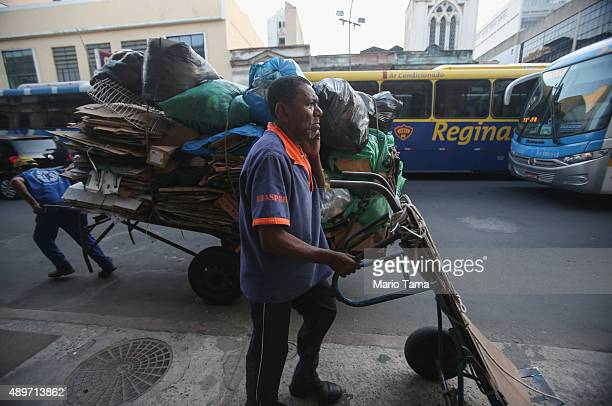 Workers walk with carts on a downtown street on September 23 2015 in Rio de Janeiro Brazil The US dollar climbed to record highs against the...