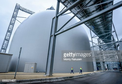 Workers walking through biomass facility, low angle view