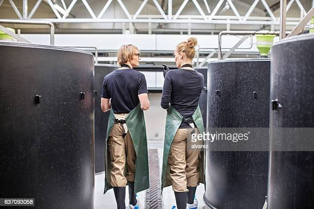 Workers walking through fish hatchery tanks