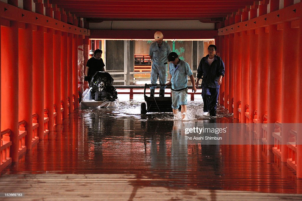 Workers walks a flooded corridor of the Itsukushima Shrine due to the heavy rain triggered by the approach of the Typhoon Sanba on September 17, 2012 in Hatsukaichi, Hiroshima, Japan.