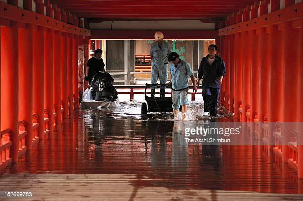 Workers walks a flooded corridor of the Itsukushima Shrine due to the heavy rain triggered by the approach of the Typhoon Sanba on September 17 2012...