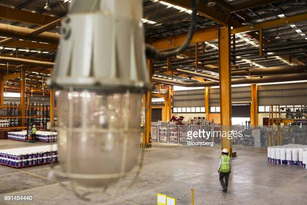 A workers walks inside a warehouse at an Akzo Nobel India Ltd paint factory in Gwalior Madhya Pradesh India on Thursday June 1 2017 Akzo Nobel NV...