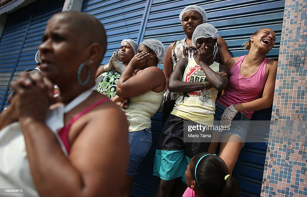 Workers (R) watch and laugh as a fellow worker holds her hands in prayer as a procession passes near the Nossa Senhora da Penha Church on the final day of the annual October feast of the patron saint marking the 378th anniversary of the church on October 27, 2013 in Rio de Janeiro, Brazil. Pilgrims often climb the entire 382 steps that lead to the church, originally constructed in 1635, which is perched on a rocky hill. Brazil holds more Catholics than any other country.