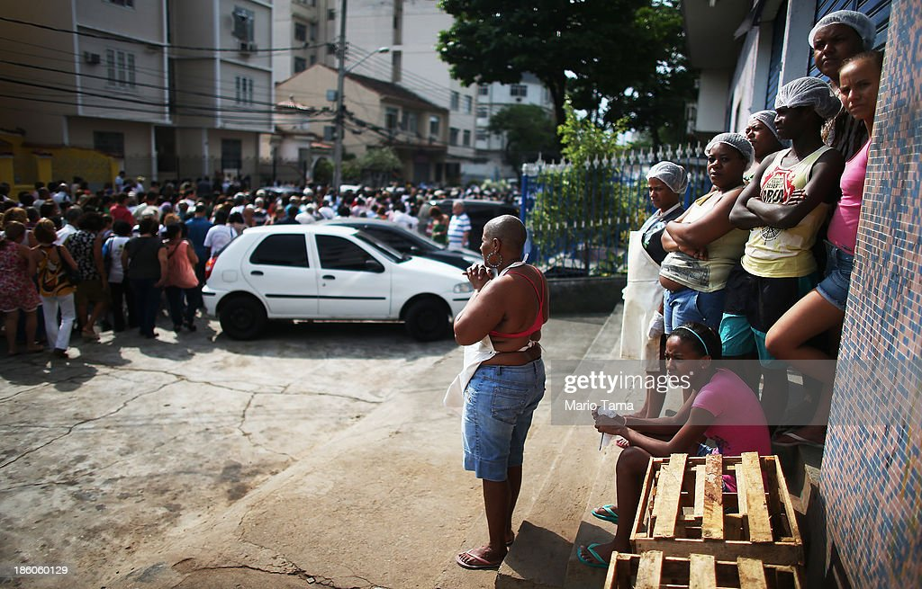 Workers (R) watch as a fellow worker holds her hands in prayer as a procession passes near the Nossa Senhora da Penha Church on the final day of the annual October feast of the patron saint marking the 378th anniversary of the church on October 27, 2013 in Rio de Janeiro, Brazil. Pilgrims often climb the entire 382 steps that lead to the church, originally constructed in 1635, which is perched on a rocky hill. Brazil holds more Catholics than any other country.