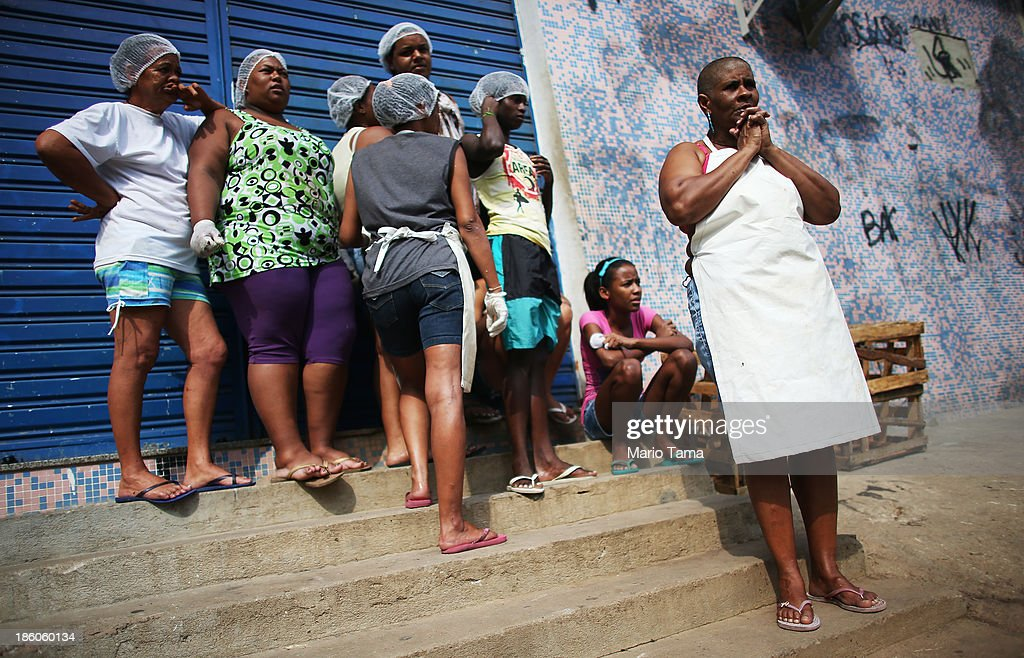 Workers watch as a procession passes near the Nossa Senhora da Penha Church on the final day of the annual October feast of the patron saint marking the 378th anniversary of the church on October 27, 2013 in Rio de Janeiro, Brazil. Pilgrims often climb the entire 382 steps that lead to the church, originally constructed in 1635, which is perched on a rocky hill. Brazil holds more Catholics than any other country.