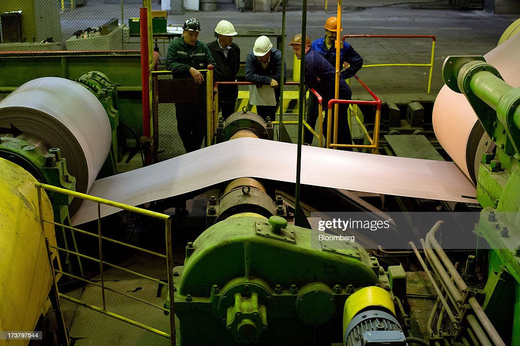 Workers watch as steel sheeting is wound into drums on a machine at OAO Mechel's metallurgical plant in Chelyabinsk, Russia, on Wednesday, July 17, 2013. Mechel, the country's largest producer of coking coal for steelmakers has begun operating its $700m rail production line which can produce 100 meter rails. Photographer: Andrey Rudakov/Bloomberg via Getty Images