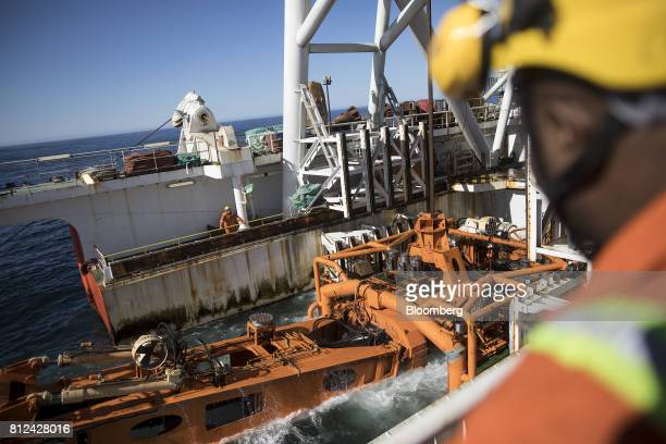 Workers watch as the 'crawler' tractor is lowered into the sea from the deck of the Mafuta diamond mining vessel operated by Debmarine Namibia a...