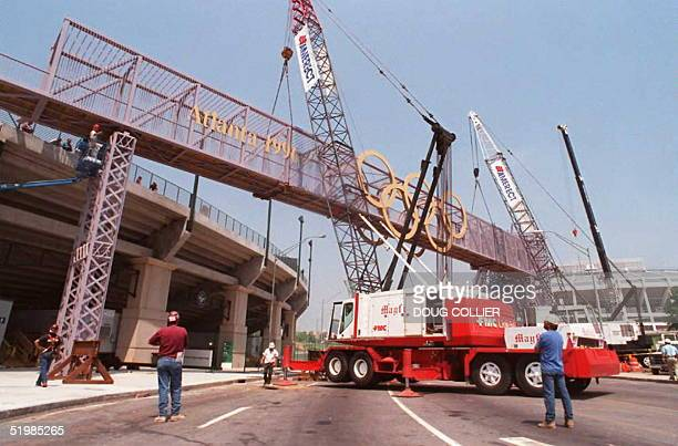 Workers watch as the Olympic Cauldron bridge is lifted into place 24 May at the Centennial Olympic Stadium in Atlanta Ga The Bridge will connect the...