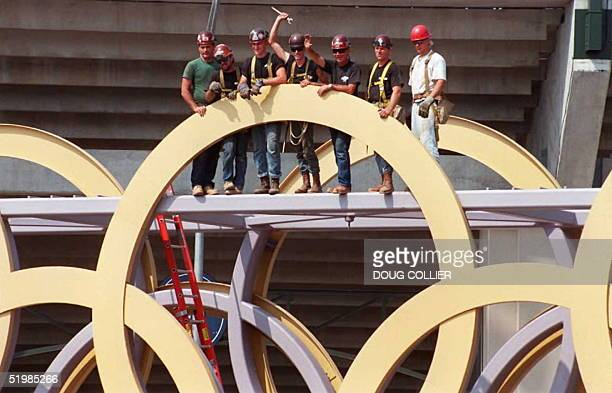 Workers wave from behind 16 foot rings that adorn the Olympic Cauldron Bridge shortly before it was lifted into place 24 May at the Centennial...