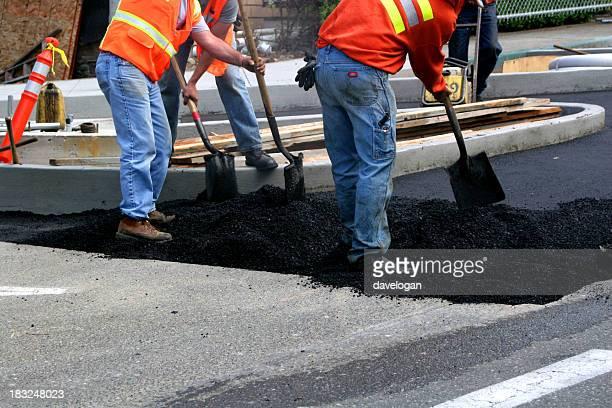 Workers wearing jeans shoveling asphalt over older pavement