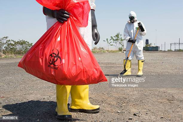 Workers wearing protective clothing removing hazardous waste