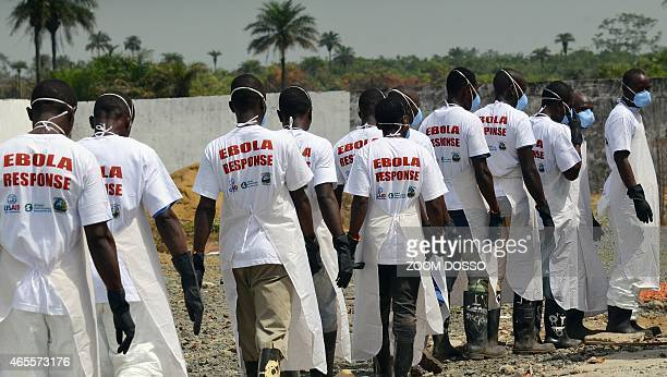 Workers wearing protective equipment march in line to go put the barrels containing victims of Ebola's remains in a car on March 7 2015 at the...
