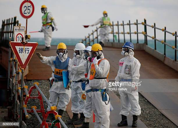 Workers wearing protective suits and masks are seen near the No 3 and No4 reactor buildings during a media tour of Tokyo Electric Power Co's...