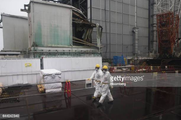 Workers wearing protective suits and masks walk past the Unit 4 reactor building at Tokyo Electric Power Co's Fukushima Daiichi nuclear power plant...
