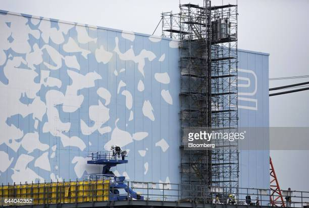 Workers wearing protective suits and masks work on the Unit 2 reactor building at Tokyo Electric Power Co's Fukushima Daiichi nuclear power plant in...