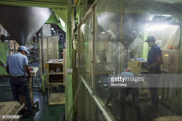 Workers weigh and pack finished plastic pellets in the packaging area at Dainichi Color India Pvt's factory in the Rajasthan State Industrial...