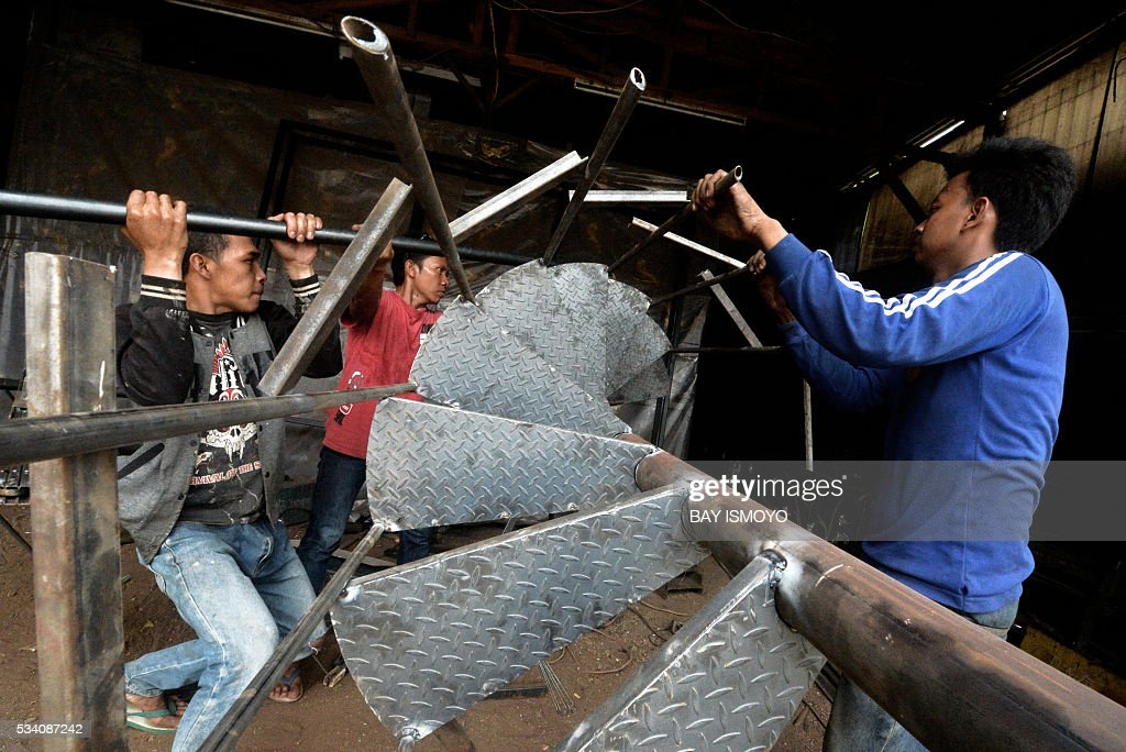 Workers weld pieces of a circular stairway together at a workshop in Jakarta on May 25, 2016. Indonesia has opened a string of new sectors to foreign businesses to attract more investment and help pull Southeast Asia's biggest economy out of a slowdown, an official said. / AFP / BAY