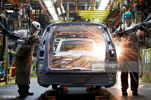 Workers weld the frame of a General Motors Co Chevrolet Zafira minivan on an assembly line at the General Motors do Brasil manufacturing plant in Sao...
