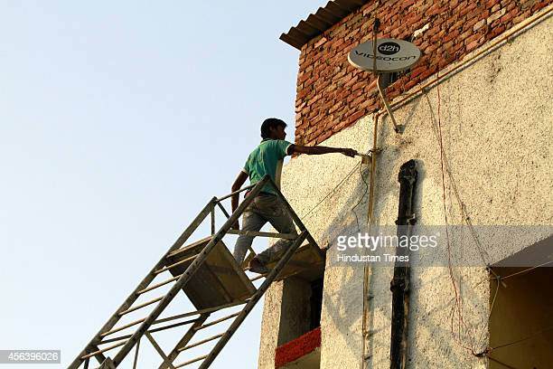 Workers whitewash the flats at Valmiki Colony ahead of PM Narendra Modis visit on September 30 2014 in New Delhi India Modi will launch the Swachh...