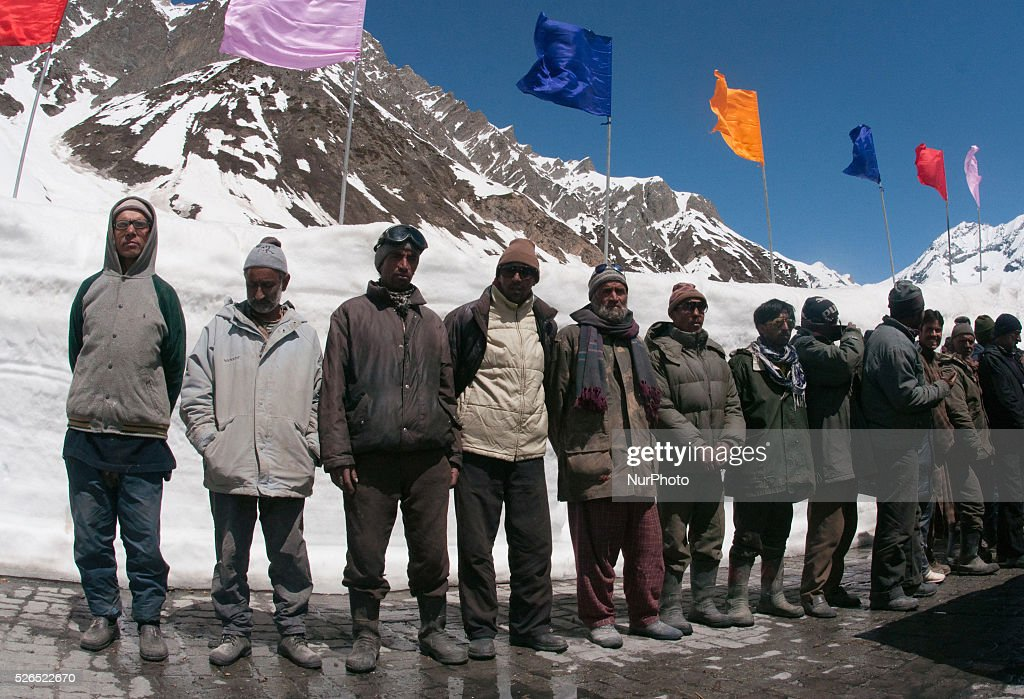 Workers who cleared the highway stand in queue as they look towards the traffic passing through the through the snow cleared Srinagar-Leh highway in Zojila, 108 km (67 miles) east of Srinagar, the summer capital of Indian controlled Kashmir, India. on April 30, 2016. The 443 km (275 mile) long highway was opened for the season by Indian Army authorities after the remaining snow at Zojila Pass, some 3,530 metres (11,581 feet) above sea level, had been cleared. The pass connects Kashmir with the Buddhist-dominated Ladakh region, a famous tourist destination known for its monasteries, landscapes and mountains.