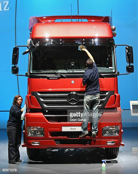Workers wipe down a heavy truck at the Daimler stand at the IAA commercial vehicles trade fair on September 23 2008 in Hanover Germany The IAA...