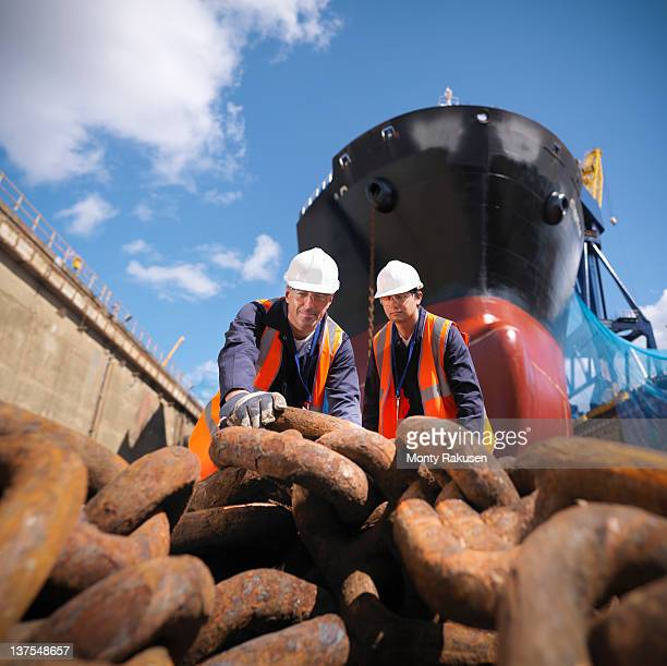 Workers with anchor chain in dry dock