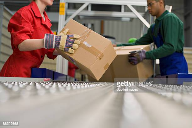 Workers with boxes and conveyor belt