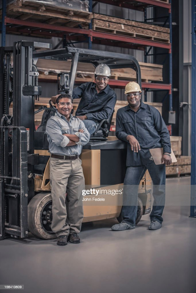 Workers with forklift in factory : Stock Photo