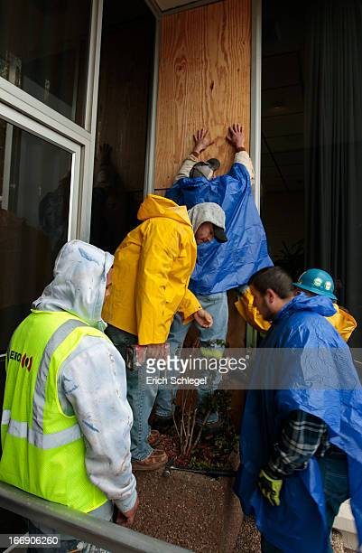 Workers with Gate Precast cover a broken window at Pointwest Bank with plywood on April 18 2013 in downtown West Texas The damage was caused by the...