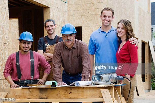 Workers with Homeowners by New House