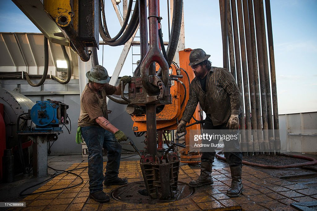 Workers with Raven Drilling line up pipe while drilling for oil in the Bakken shale formation on July 23 2013 outside Watford City North Dakota North...
