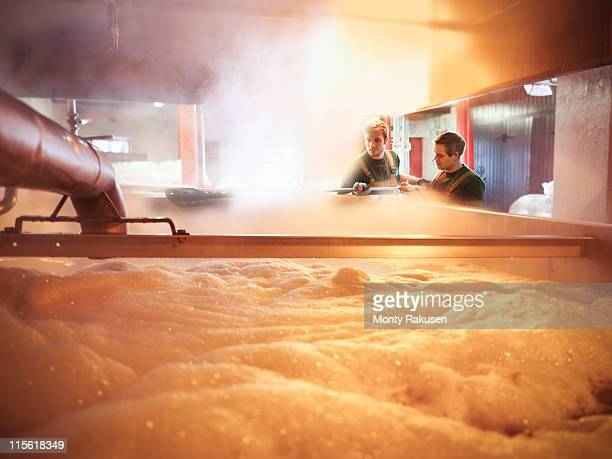 Workers with tank of hot wort in brewery