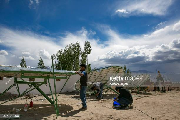 Workers with the Ladakh Renewable Energy Development Agency work to repair a solar thermal dish at a school in Choglamsar on June 12 2017 in Ladakh...