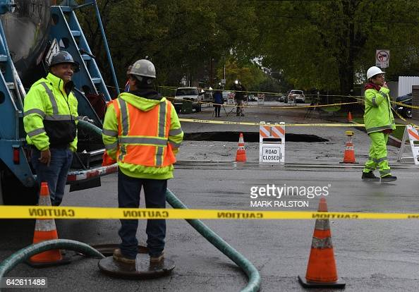 Workers work after large 20footdeep sinkhole swallowed two vehicles in North Laurel Canyon Blvd in Los Angeles is cordonedoff on February 18 after a...