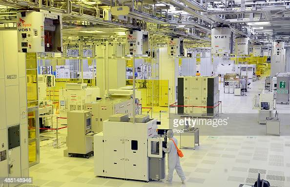 Workers work at SK HYNIX Inc plant on August 25 2015 in Icheon South Korea South Korean chip giant SK Hynix Inc said on August 25 2015 that it will...