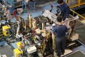 Workers work on an engine assembly line for a Hyundai trucks and bus at the JeonJu plant on October 17 2007 in JeonJu South Korea Hyundai Motor Co...