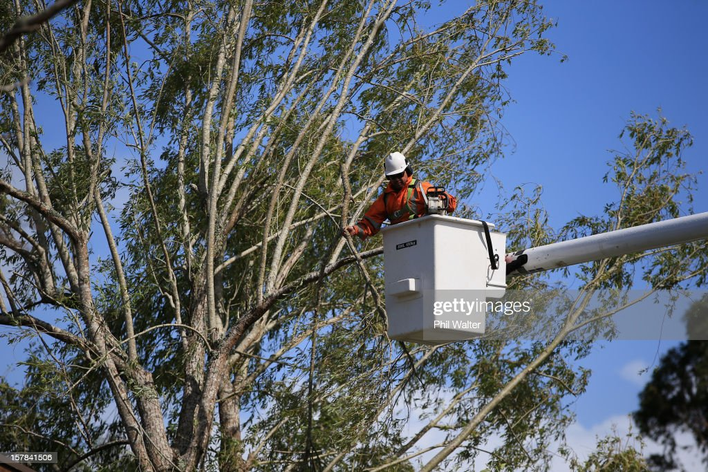 Workers work to repair the power supply to the Auckland suburb of Whenuapai following a tornado that struck yesterday on December 7, 2012 in Auckland, New Zealand. Police today named the three men killed whilst working on a construction site when the tornado hit.