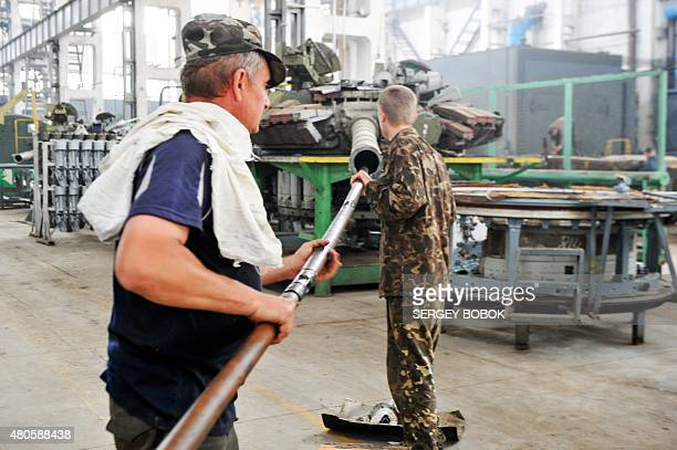 Workers work to upgrade T80 tanks at the Malyshev Tank Factory in the northeastern Ukrainian city of Kharkiv on July 13 to be handed to Ukrainian...