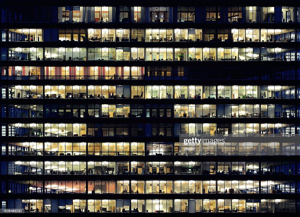 Les travailleurs travaillant tard. BUREAU, FENÊTRES par nuit. : Photo