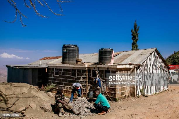Workers working with stones next to a hut which is painted in the colors of a Zebra am Rift Valley View Point Nahe Nairobi on October 08 2017 in...