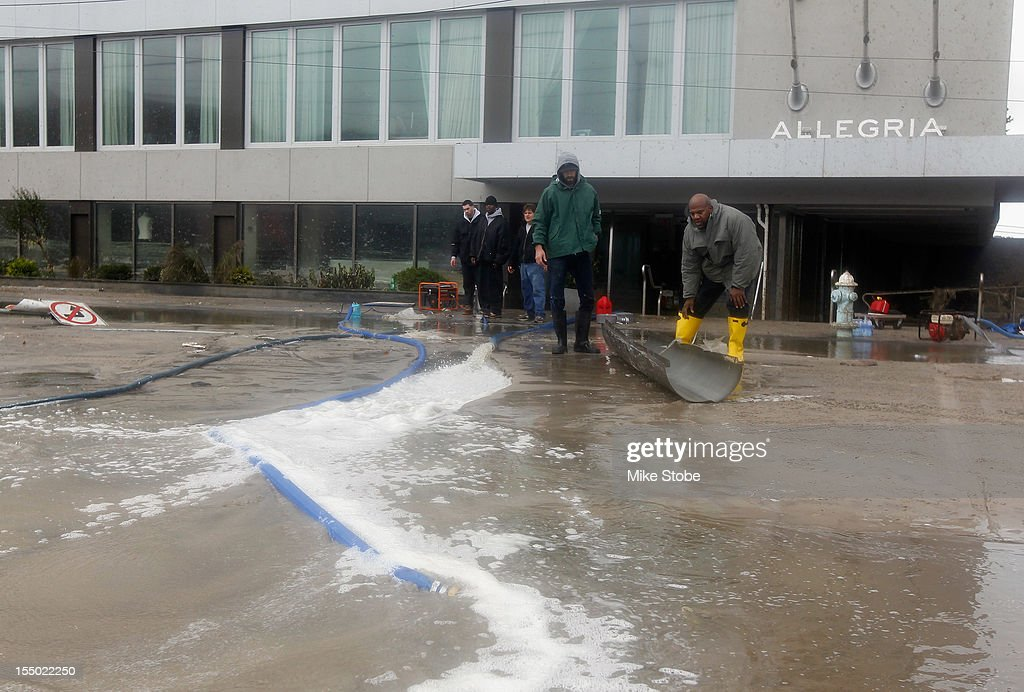 Workes pump water out of the Allegria Hotel lobby on October 30 2012 in Long Beach New York The storm has claimed at least 40 lives in the United...
